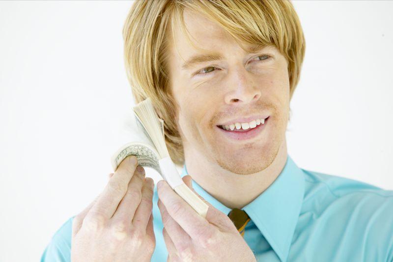 Man fanning money next to ear