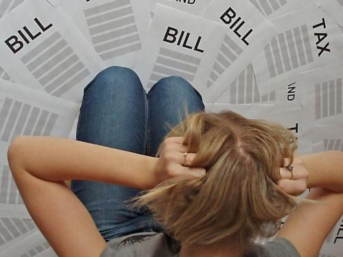 woman looking at a lot of bills