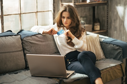 woman holding a credit card while looking at laptop